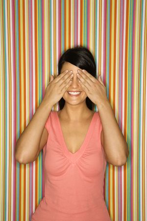 covering: Young adult female Caucasian covering eyes on striped background.