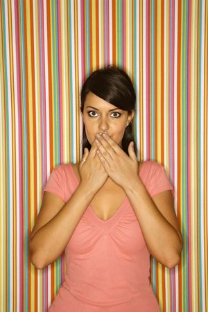 speechless: Young adult female Caucasian covering mouth on striped background. Stock Photo