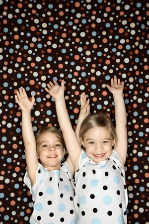 alike: Female children Caucasian twins looking at viewer with arms raised. Stock Photo
