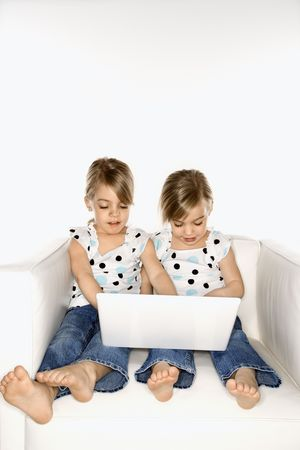 Female children Caucasian twins playing with laptop computer. photo