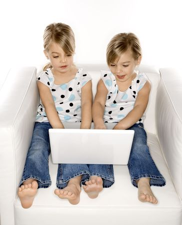 pessoas: Female children Caucasian twins playing with laptop computer.