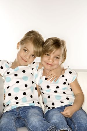 Female children Caucasian twins sitting together on chair. Stock Photo - 2457189