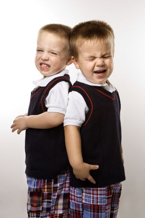 pessoas: Caucasian twin boys crying standing against white background. Imagens