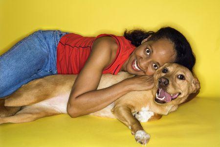 prime adult: African American prime adult female hugging dog.