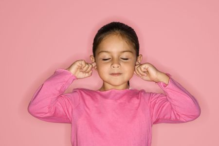 Female Hispanic girl with fingers in ears and eyes closed. photo