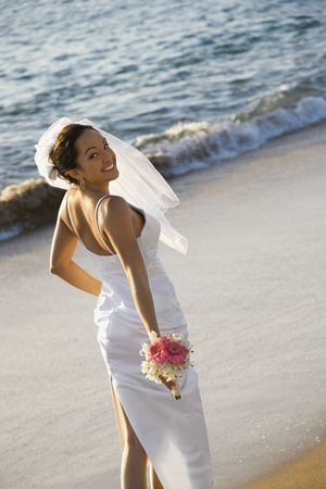 Young adult female Caucasian bride standing on beach. photo