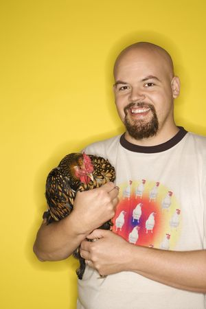 prime adult: Caucasian mid-adult man holding Golden Laced Wyandotte chicken.