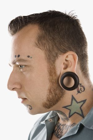 Caucasian mid-adult man with tattoos and piercings. Stock Photo