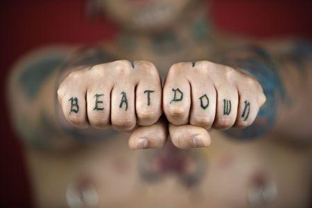 feindschaft: Kaukasischen Mitte der erwachsenen Mann mit Tattoos und Piercings Betrieb heraus F�uste Lesung beat down.  Lizenzfreie Bilder