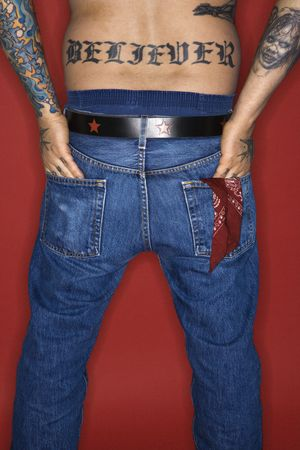 Caucasian mid-adult man back view with tattoo reading believer.