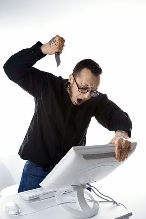 stabbing: Caucasian mid-adult man with tattoos and piercings stabbing computer with knife. Stock Photo