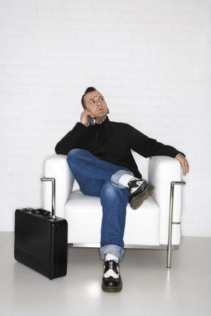 nonconformity: Caucasian mid-adult man with tattoos and piercings talking on cell phone with briefcase.