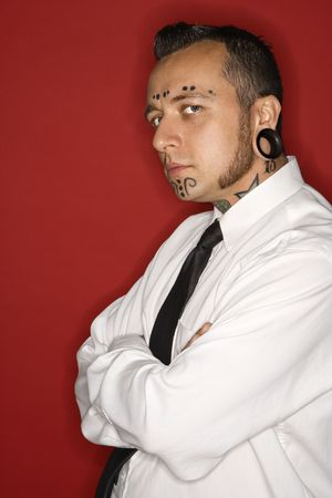 nonconformity: Caucasian mid-adult man with tattoos and piercings wearing necktie looking at viewer. Stock Photo
