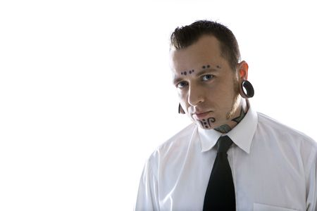 nonconformity: Caucasian mid-adult man with tattoos and piercings wearing necktie.
