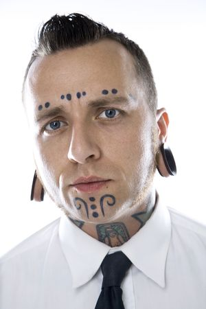 tattoo face: Caucasian mid-adult man with tattoos and piercings wearing necktie.