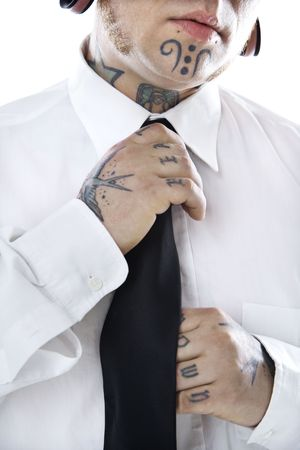 nonconformity: Caucasian mid-adult man with tattoos and piercings adjusting necktie.