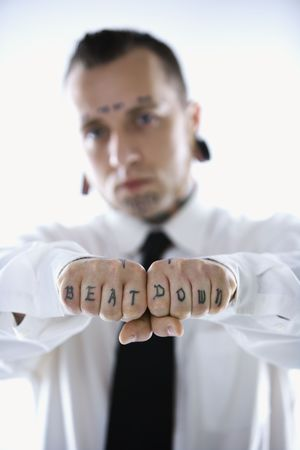 hoodlum: Caucasian mid-adult man with tattoos and piercings holding out fists reading beat down.