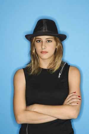 nonconformity: Caucasian young adult female wearing hat with arms crossed.