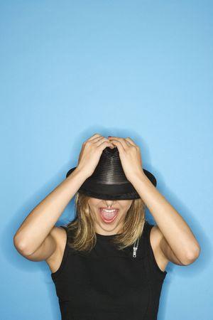 Caucásicos jóvenes mujeres adultas sombrero tirando abajo sobre los ojos.  Foto de archivo - 2479183