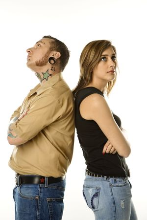 Caucasian mid-adult man and teen female standing back to back. photo