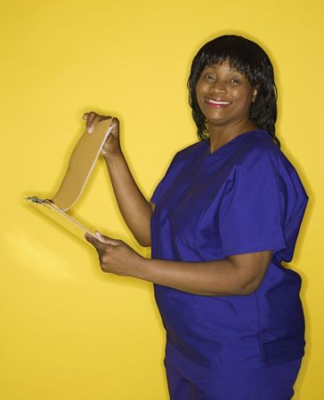 African-American  mid-adult woman in medical uniform smiling reading chart. Stock Photo - 2478814