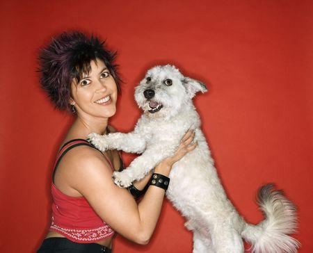 nonconformity: Hispanic young adult female holding small white dog.