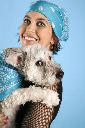 alike: Hispanic mid-adult woman holding small white dog wearing matching bandanas.