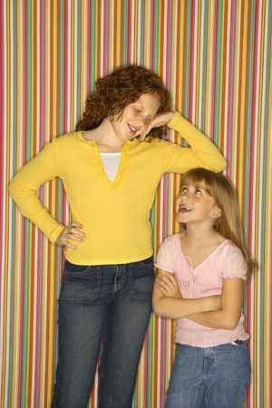 Caucasian female child leaning on smaller female child. Stock Photo - 2479275