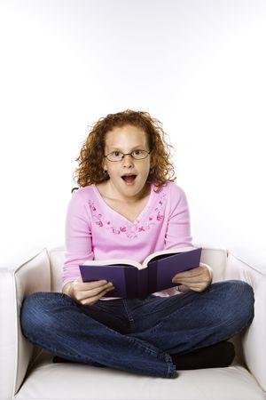Caucasian female child sitting reading book looking surprised. Stock Photo - 2478811