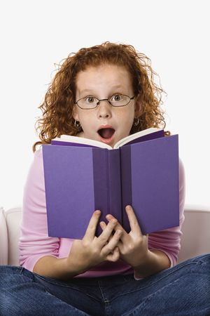 Caucasian female child sitting reading book looking surprised. Stock Photo - 2479131