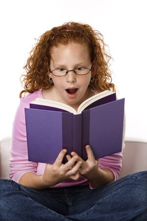 Caucasian female child sitting reading book looking surprised. Stock Photo - 2479177