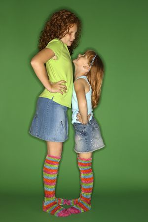 Caucasian female children standing face to face looking at each other. Stock Photo - 2479113