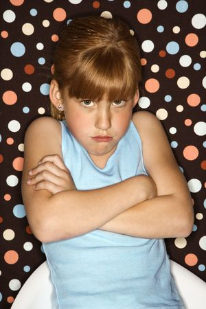 to sulk: Caucasian female child pouting with arms crossed.