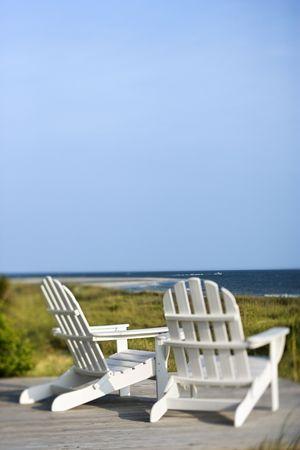 strandstoel: Adirondack stoelen op het dek op zoek naar strand op Bald Head Island, North Carolina. Stockfoto