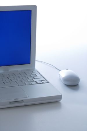 Laptop computer with blue screen and mouse. photo