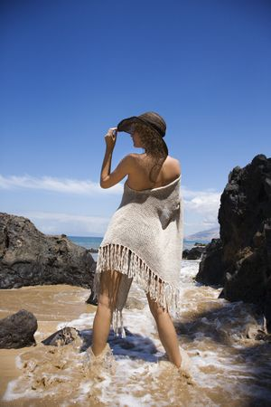 Young adult female Caucasian standing in water on beach tilting brimmed hat. photo