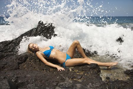 wet suit: Young adult female Caucasian lying on rock in bikini with wave crashing.