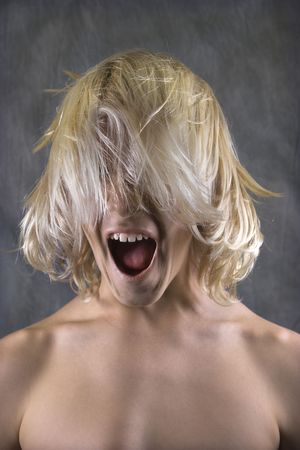 Male Caucasian teen with hair over face screaming.