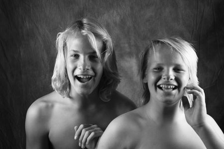 Caucasian adolescent and pre-teen brothers looking at viewer laughing.