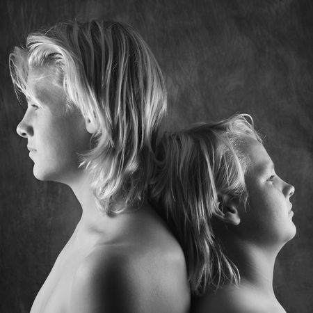 taller: Male Caucasian adolescent and teen brothers standing back to back. Stock Photo
