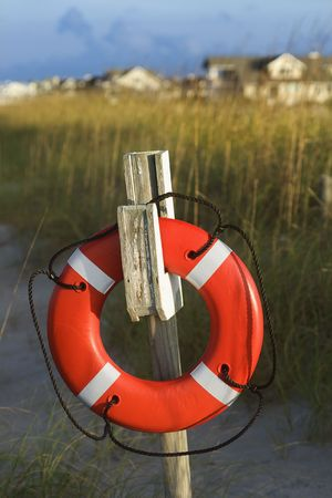 life preserver: Life preserver hanging on post on beach.