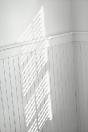 moulding: Sun spot on wall from light shining through window blinds.