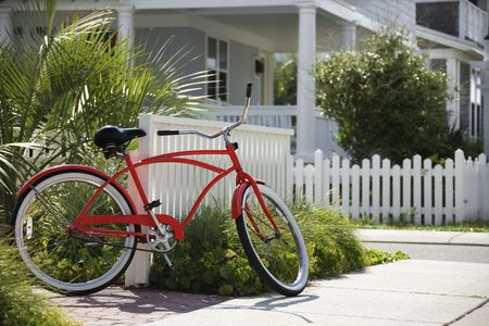 cruiser bike: Red beach cruiser bicycle propped against fence in front of house.