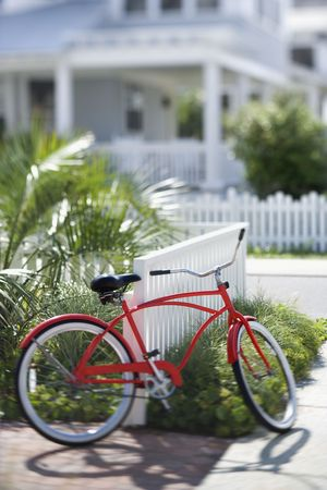 beach cruiser: Red beach cruiser bicycle propped against fence in front of house.