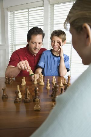 two people with others: Caucasian mid-adult mother watching mid-adult dad teaching chess to pre-teen son.