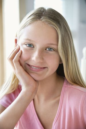 preteen girl: Portrait of Caucasian pre-teen girl looking at viewer resting chin in hand and smiling.