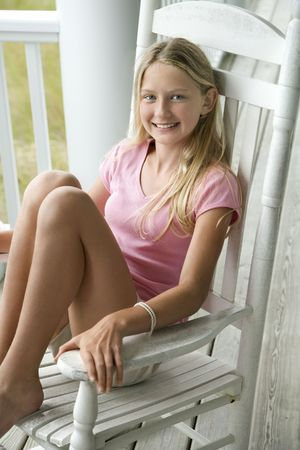 Caucasian pre-teen girl sitting in rocking chair on porch smiling.