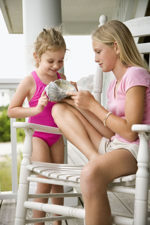 Caucasian pre-teen girl showing conch shell to other Caucasian female child. photo