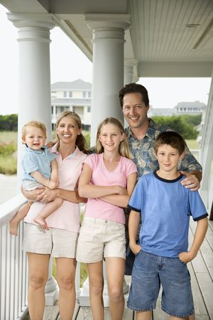 Family portrait of Caucasian mid-adult man and woman with pre-teen girl and boy and male toddler, standing on porch. photo