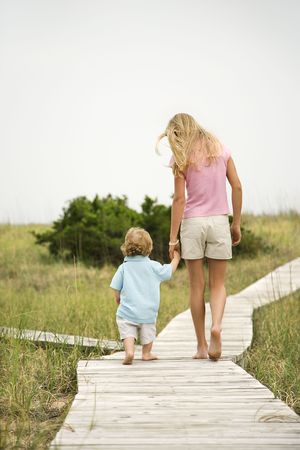 taller: Caucasian pre-teen girl walking on beach access walkway and holding hands with Caucasian male toddler .